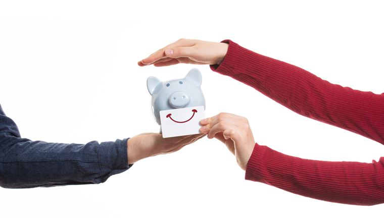 Close up of man and woman hands protecting a piggy bank with smile sticker isolated on white. Business partnership and collaboration. Concept for protecting your assets, financial help and insurance.